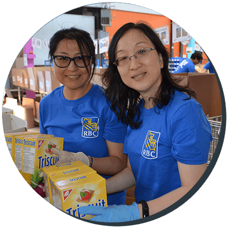 Two women volunteers from the Royal Bank sorting food